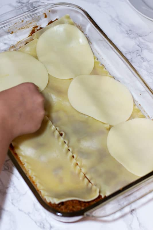 Provolone cheese slices being placed on top of cooked lasagna noodles in preparation for making lasagna.