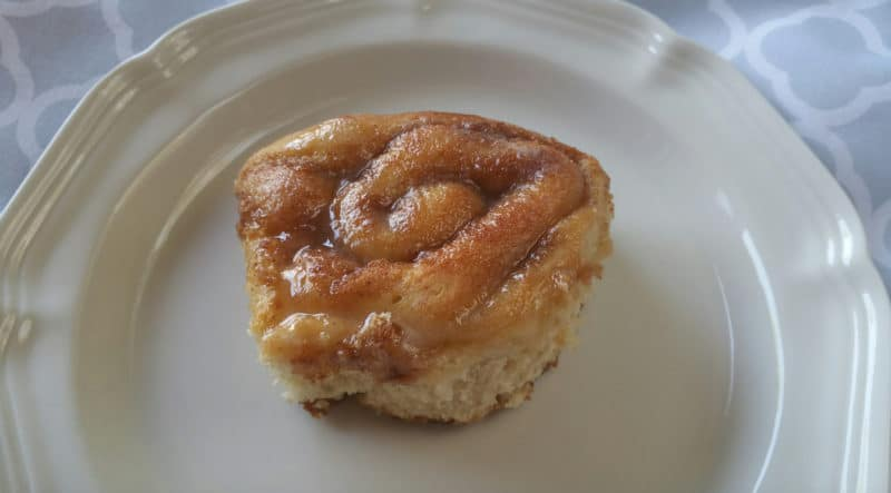 One cinnamon roll on a white plate.