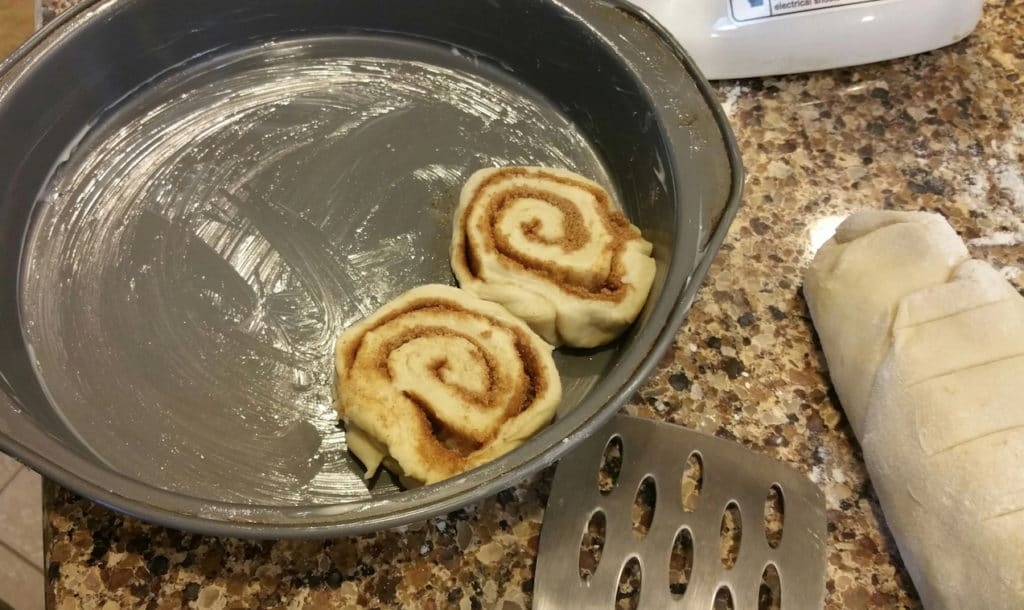 A round baking pan with two uncooked cinnamon rolls on the edge.