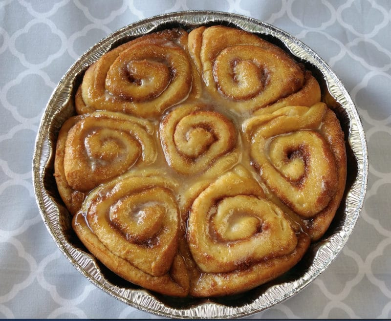 An aluminum pan with cooked cinnamon rolls on a table.
