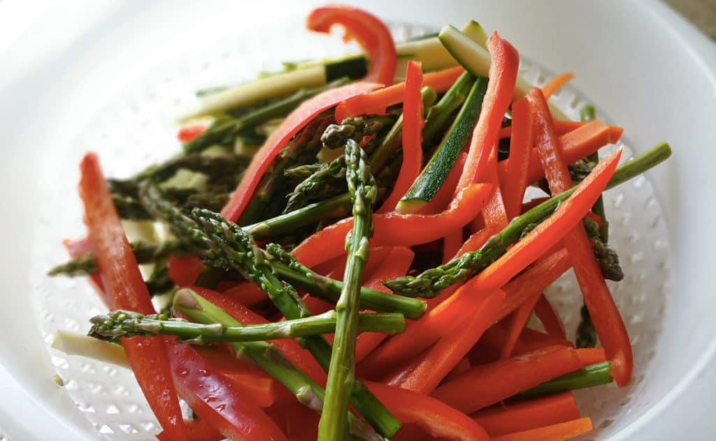 White colander containing fresh sliced carrots, asparagus, zucchini and red bell peppers.