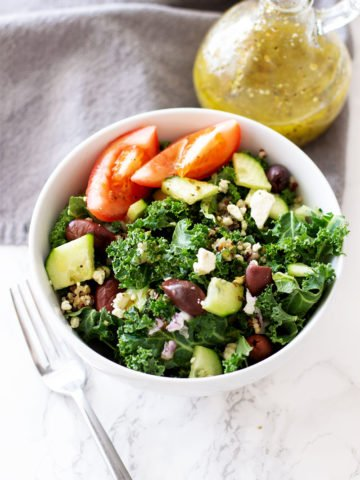 White bowl containing kale, cucumbers, feta cheese, Kalamata olive, and tomatoes, Greek salad dressing on table.