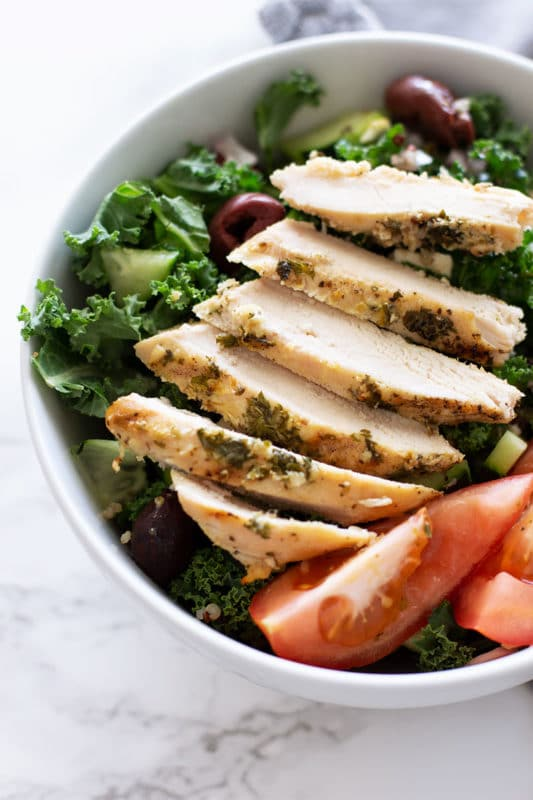 White bowl containing Greek Kale and Quinoa Salad, topped with a Greek Marinated chicken breast.