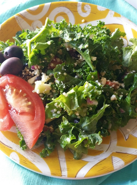 Yellow plate sitting on a blue napkin containing a kale and quinoa salad topped with olives and a tomato wedge.