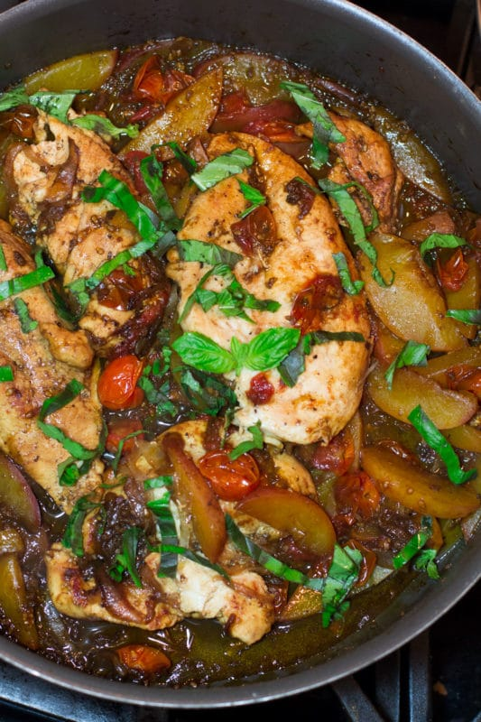 Skillet containing chicken, peaches, tomato topped with basil in a balsamic vinegar glaze.