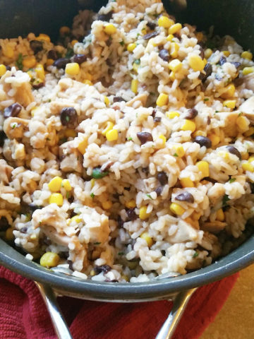 A bowl of rice, beans, corn, and chopped chicken stirred together.