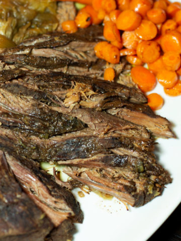Sliced brisket on a white platter with a side of carrots.