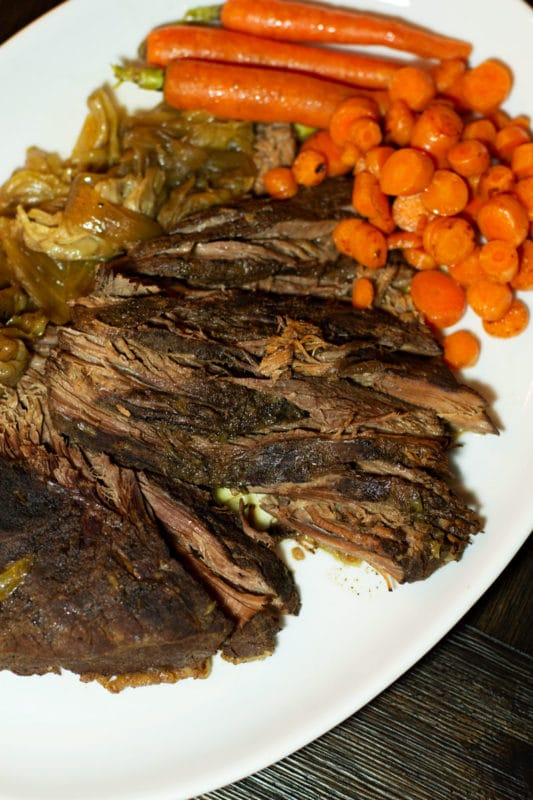 Sliced brisket on a white platter, topped with carrots and cabbage.