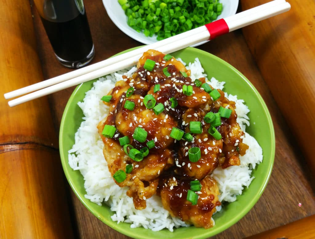 A green bowl of Asian sesame chicken on a bed of white rice sprinkled with green scallions with chopsticks.