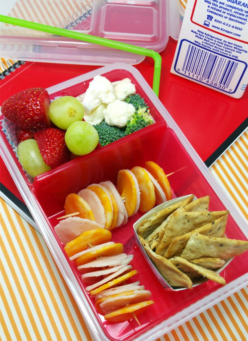 Red plastic tupperware containing a DIY School Lunch filled with turkey and cheese lunchables, strawberries, grapes, cauliflower and broccoli, carton of milk on table.