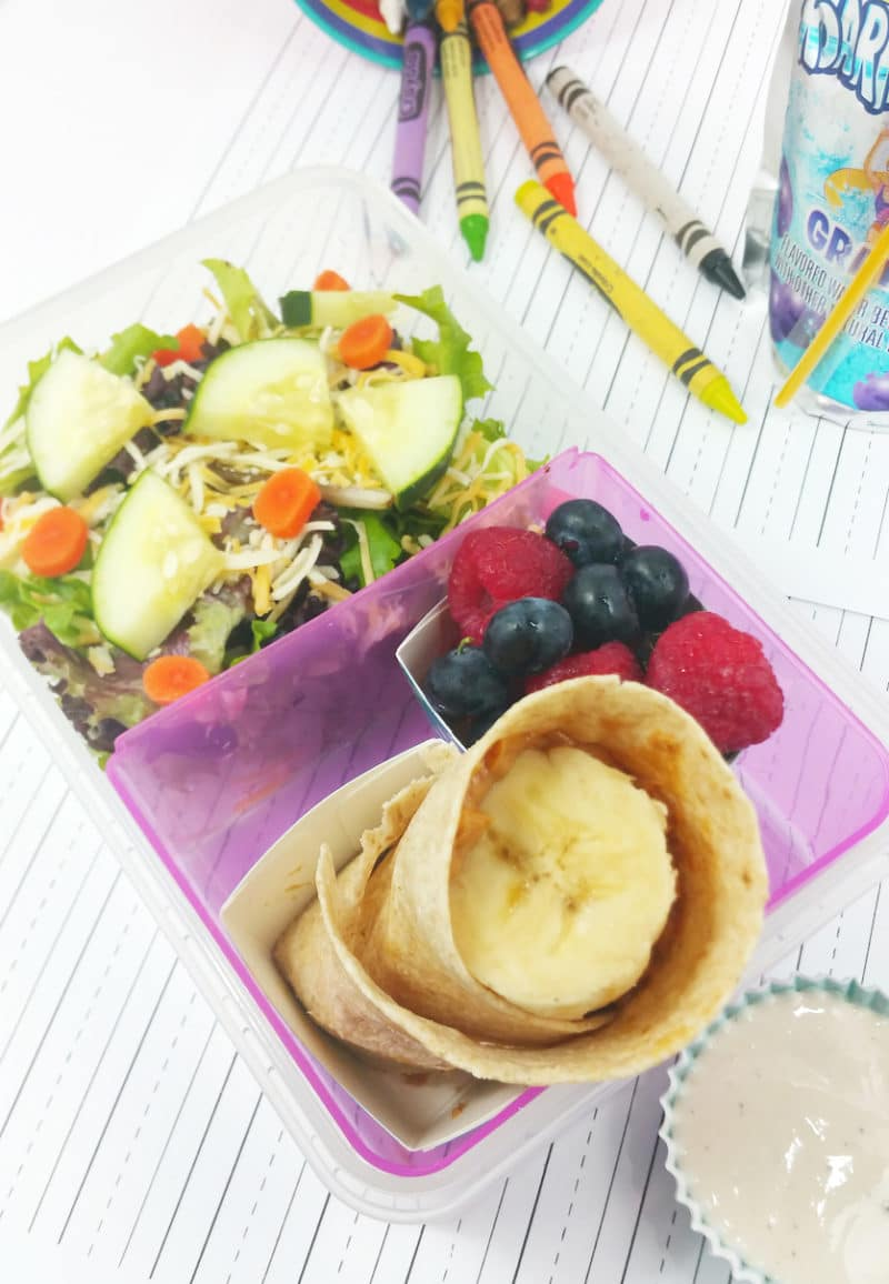 Pink plastic tupperware containing a DIY School Lunch filled with Peanut Butter and Banana wrap, side salad, raspberries and blueberries.