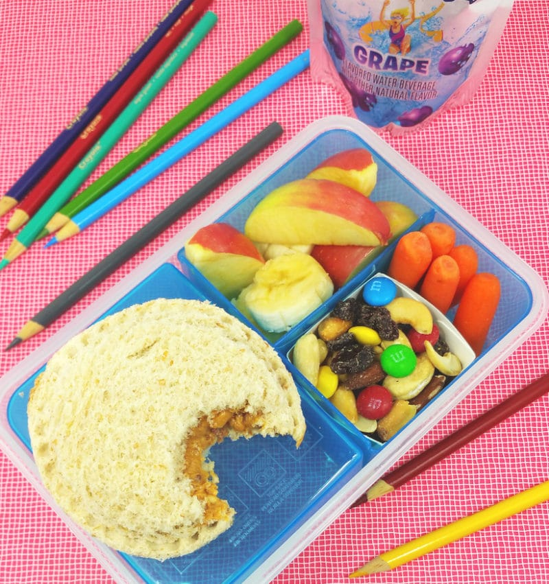 Blue plastic tupperware containing a DIY School Lunch filled with PB&J, trail mix, carrots and apple slices, colored pencils and juice box on table.