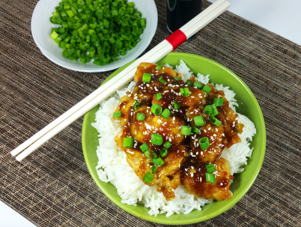 A green bowl of Asian sesame chicken on a bed of white rice with chopsticks.