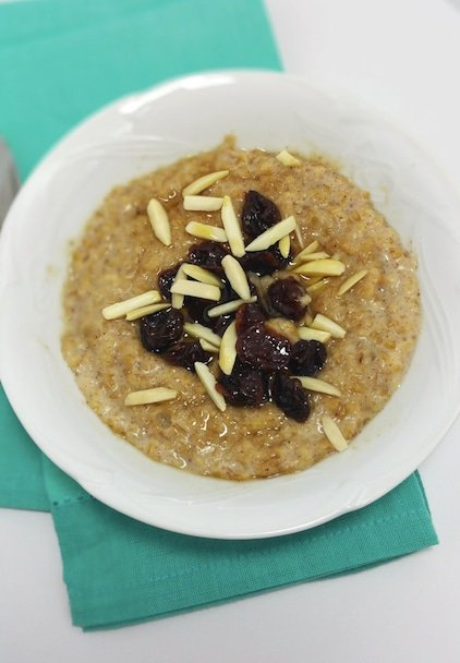 A close up of a bowl of cooked steel-cut oats, with dried cherries, cut almonds.