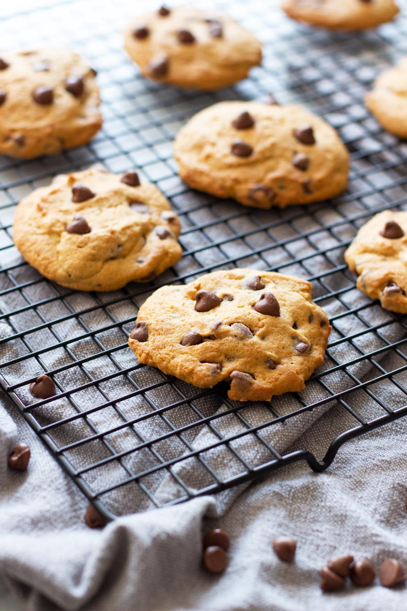 8 chocolate chip cookies cooking on a wire cooling rack, chocolate chip morsels on table.