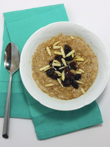 A white bowl of cooked steel-cut oats, with dried cherries, cut almonds on a green napkin.