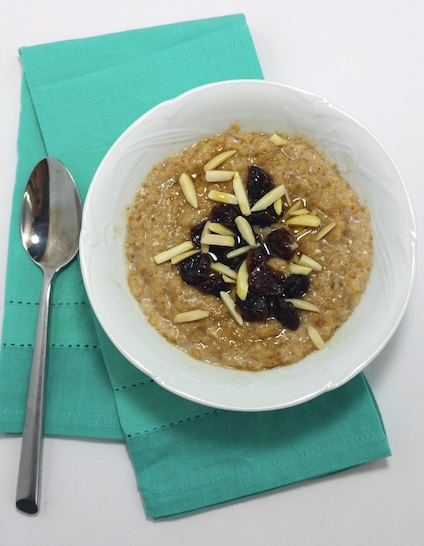 A bowl of cooked steel-cut oats, with dried cherries, cut almonds on a green napkin next to a spoon.
