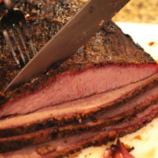 A knife slicing into a beef brisket.