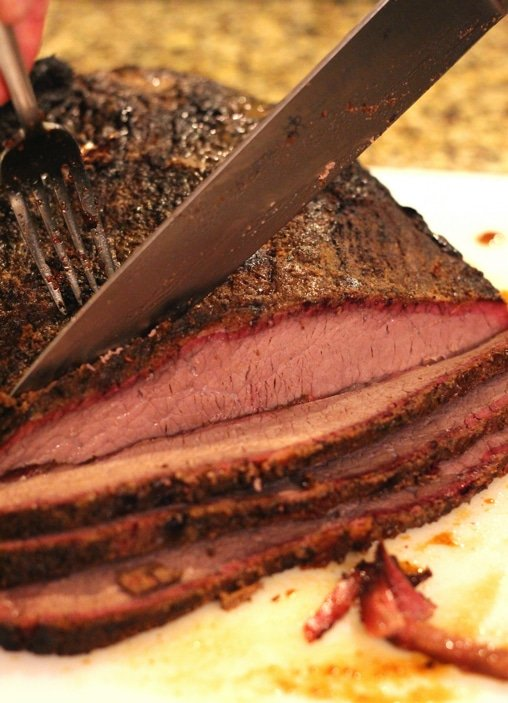 Seasoned Smoked Brisket being sliced, red smoke ring displayed in the brisket.