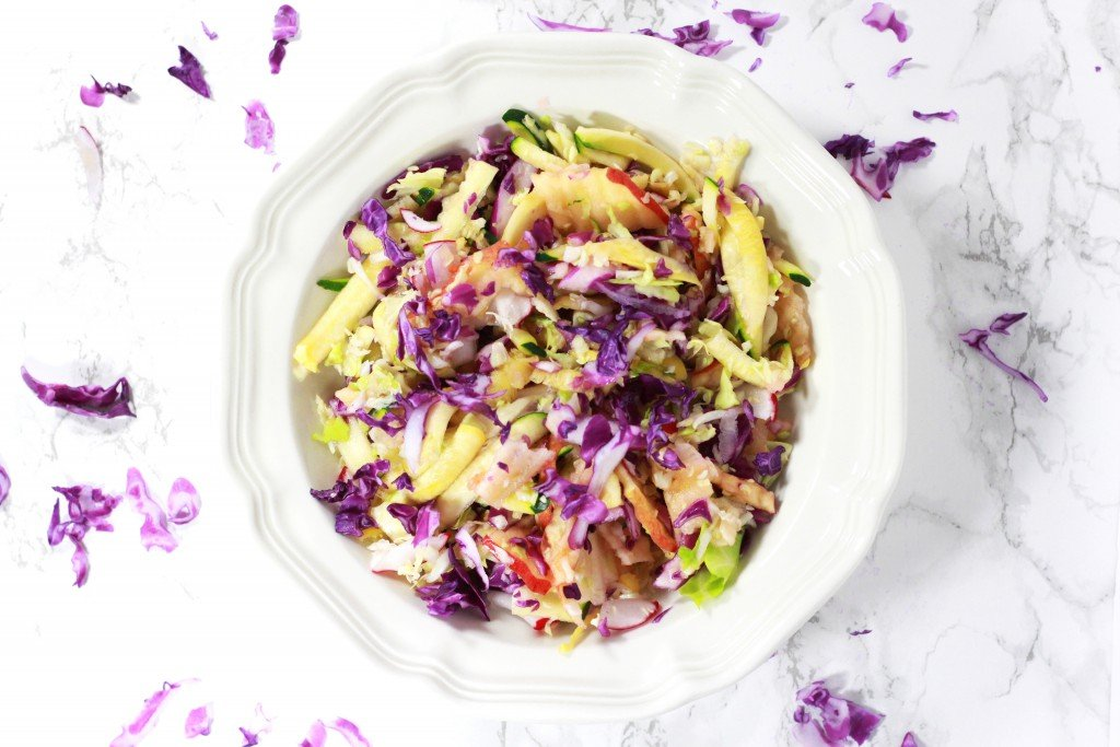 White bowl containing coleslaw with purple cabbage, squash, apple and celery, sitting on a granite table sprinkled with purple cabbage shavings.