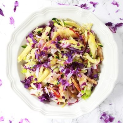 White bowl containing purple cabbage, squash, apple and celery, sitting on a white granite table, sprinkled with purple cabbage shavings.