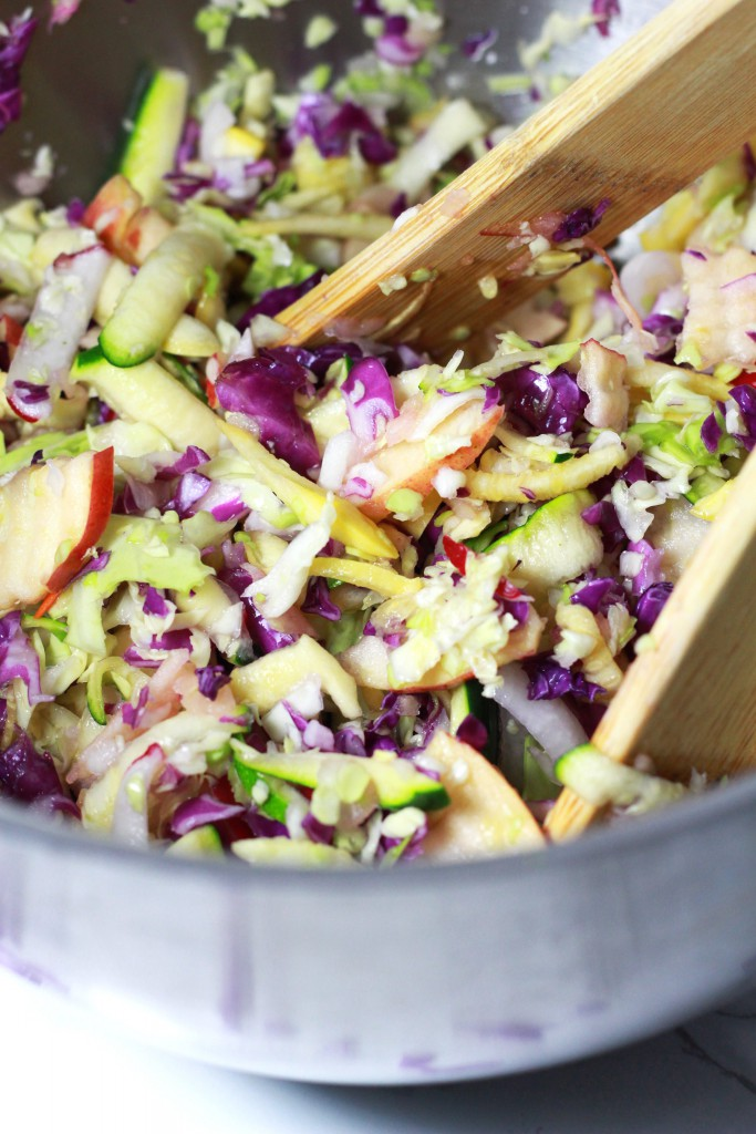 Silver mixing bowl bowl containing coleslaw with purple cabbage, squash, apple and celery; wooden tongs for serving.