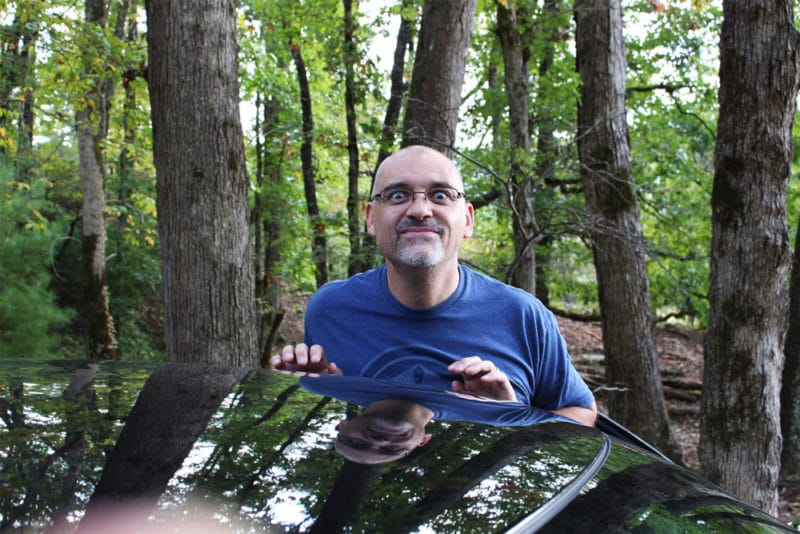 A man standing in a forest leaning on a car.
