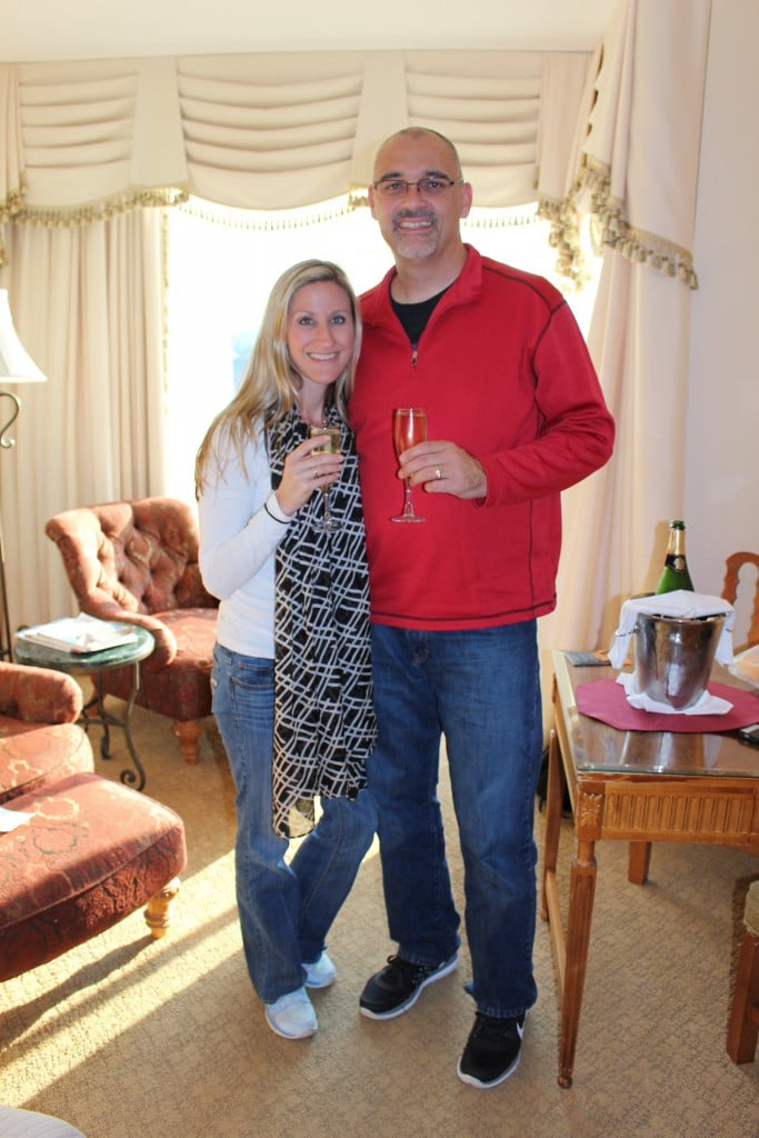 A couple toasting with champagne in a living room.