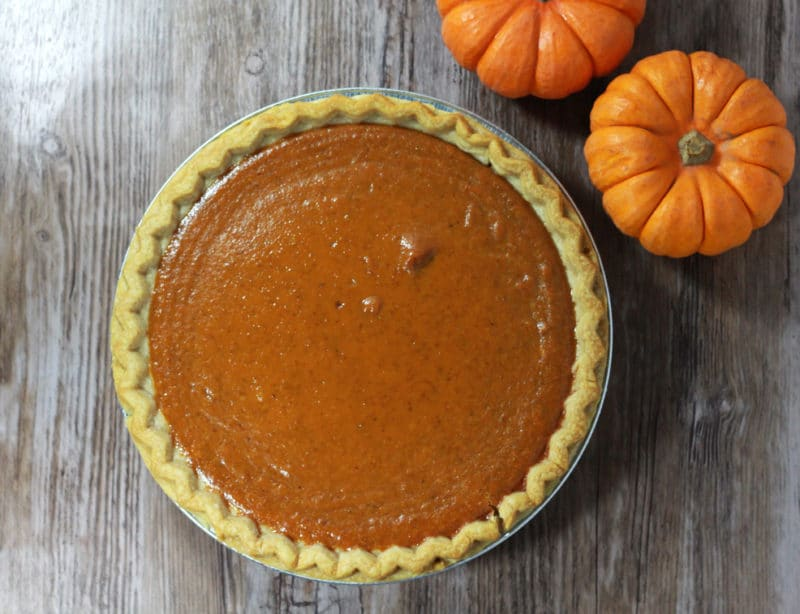 Pumpkin pie in a pie dish sitting on a wooden table, two mini pumpkins on table.