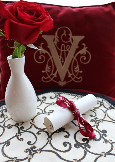 A red rose and scroll on a table with the Vanderbilt family logo in the distance.