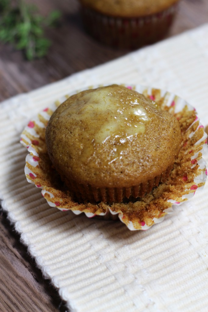 Buttered Acorn Squash Muffin sitting on a wooden table with and white tablecloth.