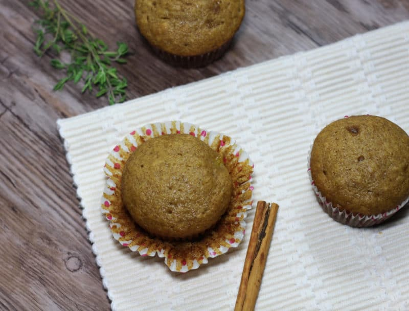 Three Acorn Squash Muffins sitting on a wooden table, two muffins on the white tablecloth with cinnamon stick on side.
