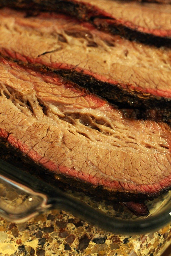 Slices of smoked brisket in a glass pyrex dish.