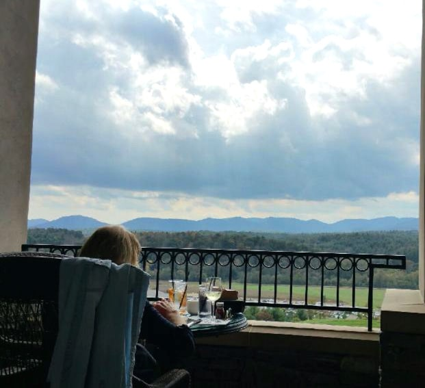 A person sitting on a balcony looking out at the horizon with clouds and mountains.