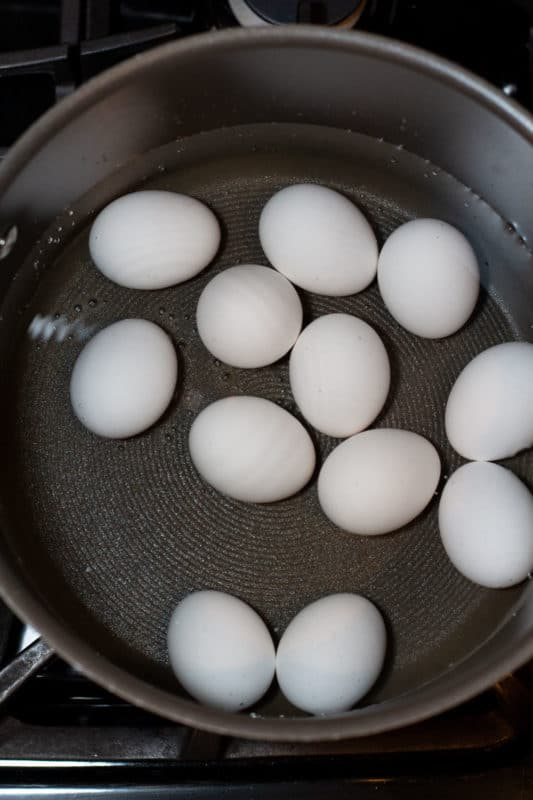 12 eggs boiling in a pot.