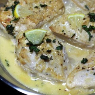 A close up of chicken smothered with a cream sauce and cut lemon on a plate.