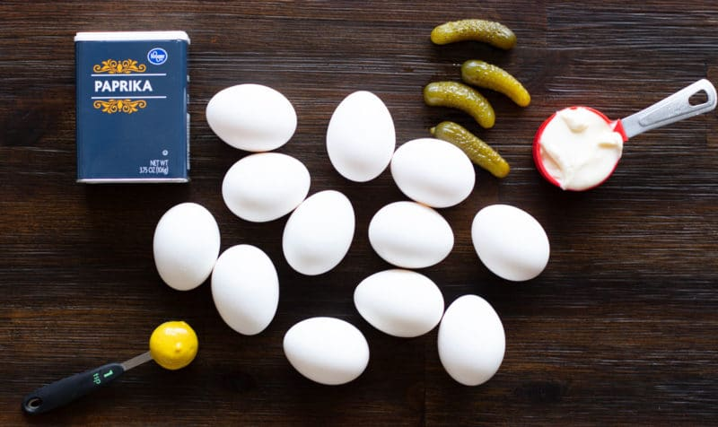 Paprika, eggs, mustard, mayonnaise and sweet pickles on a wooden table.