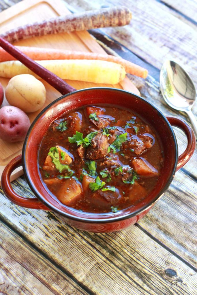 A bowl of beef stew with meat, carrots, and potatoes surrounded by carrots and potatoes on the table.