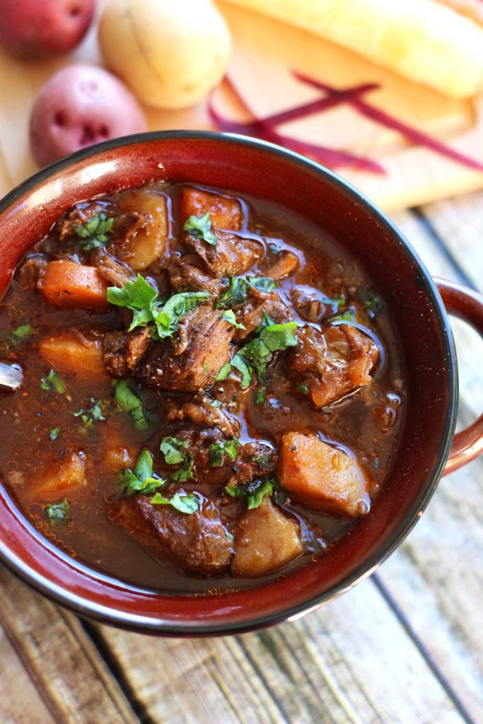 A close up of a bowl of beef stew with meat, carrots, and potatoes on a table.