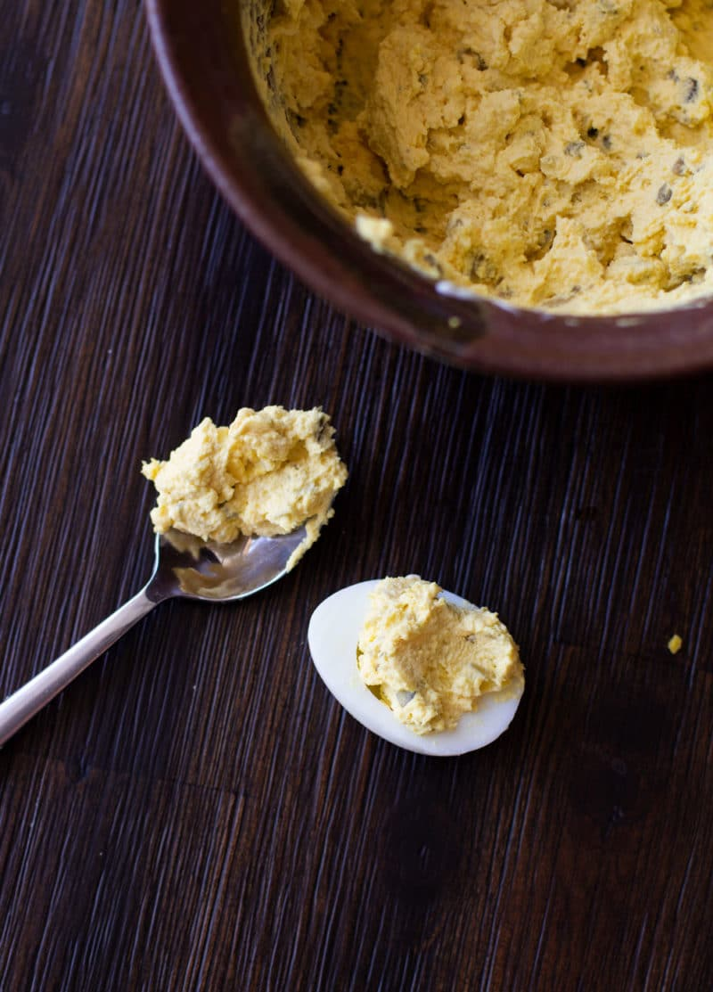 Deviled egg filling in a spoon, filled egg on table alongside bowl of filling.