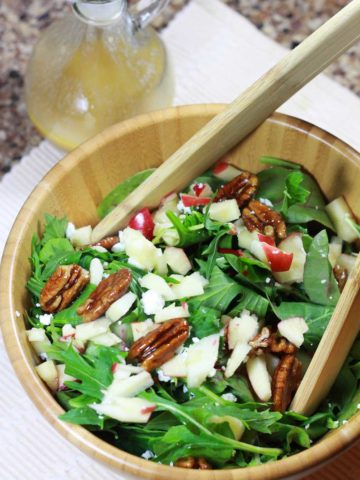 A wooden bowl of arugula salad topped with candied pecans, diced apples, and goat cheese crumbles.