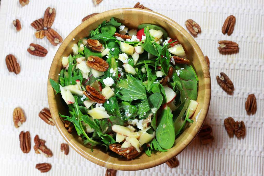A wooden bowl of mixed arugula salad topped with candied pecans, diced apples, and goat cheese crumbles.