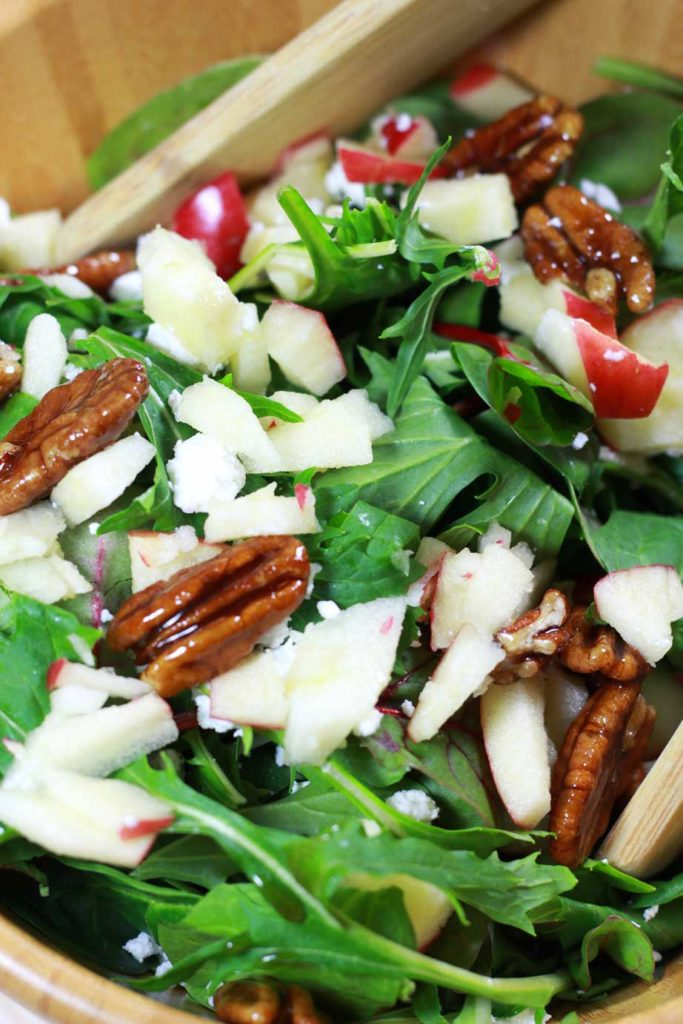 A close up of arugula salad topped with candied pecans, diced apples, and goat cheese crumbles.
