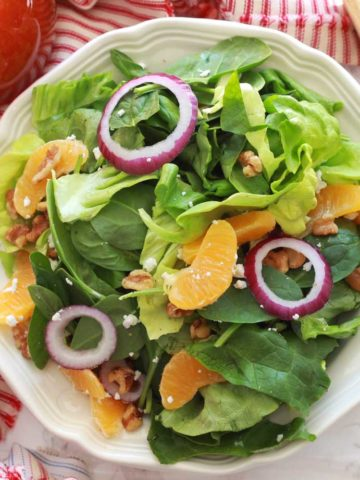 A plate of a green salad topped with red onions, walnuts and goat cheese crumbles.