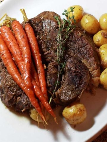 A white serving tray of a large cooked pot roast topped with carrots and surrounded by petite potatoes.