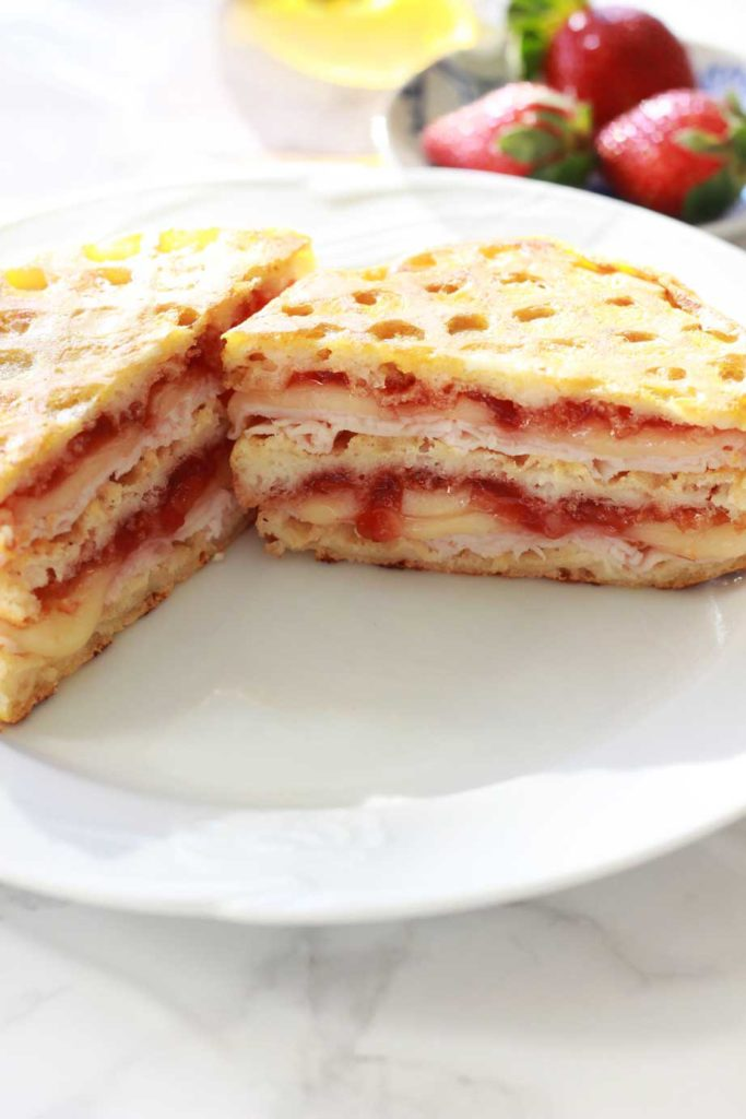 White plate containing a sliced Monte Cristo sandwich with jam, turkey and cheese, strawberries on table.