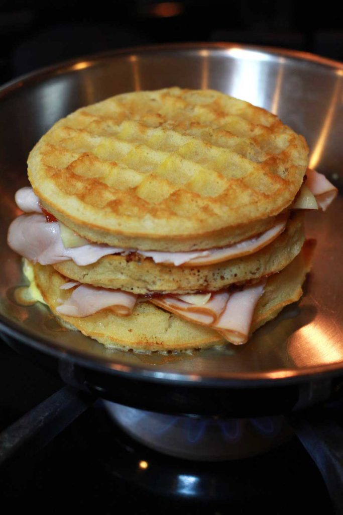 A Monte Cristo Sandwich made with turkey, cheese and waffles being toasted in a skillet.