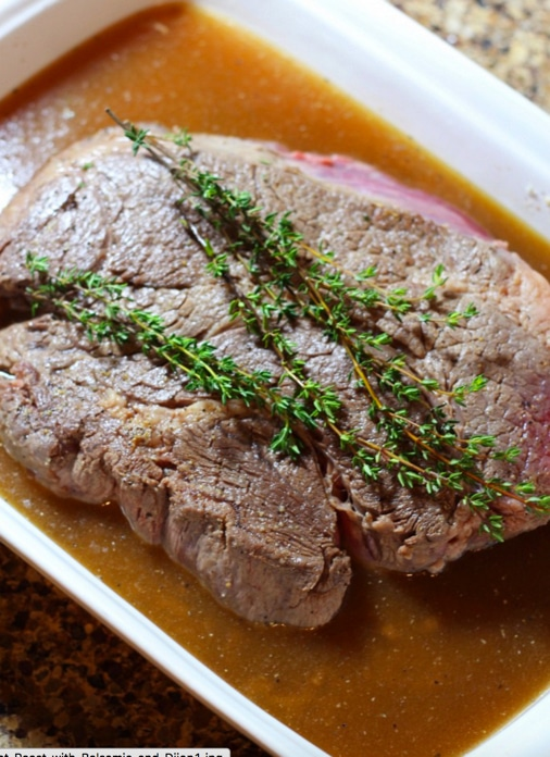 A close up of a large pot roast topped with thyme sprigs in a white dish.