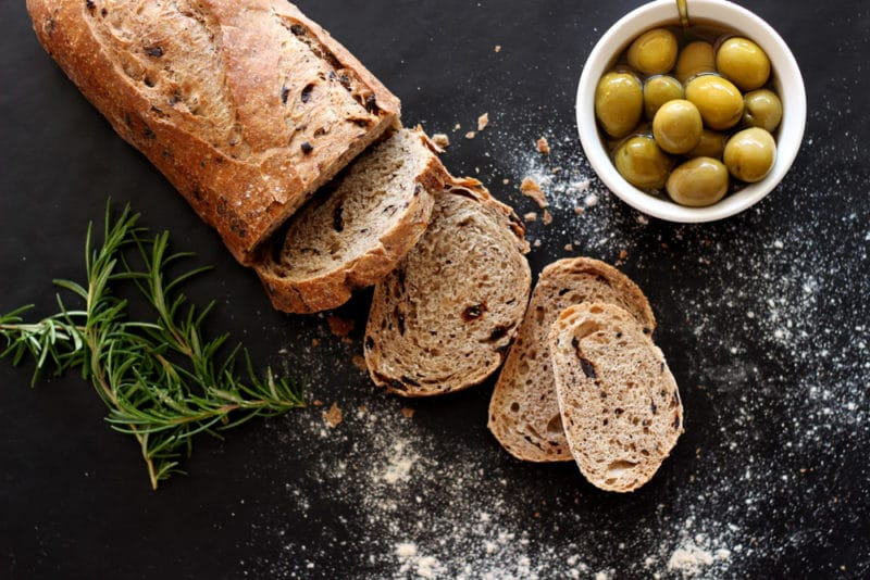 French loaf baguette sitting on a black table, fresh rosemary sprigs and a bowl of green olives on the table, sprinkled flour on table.