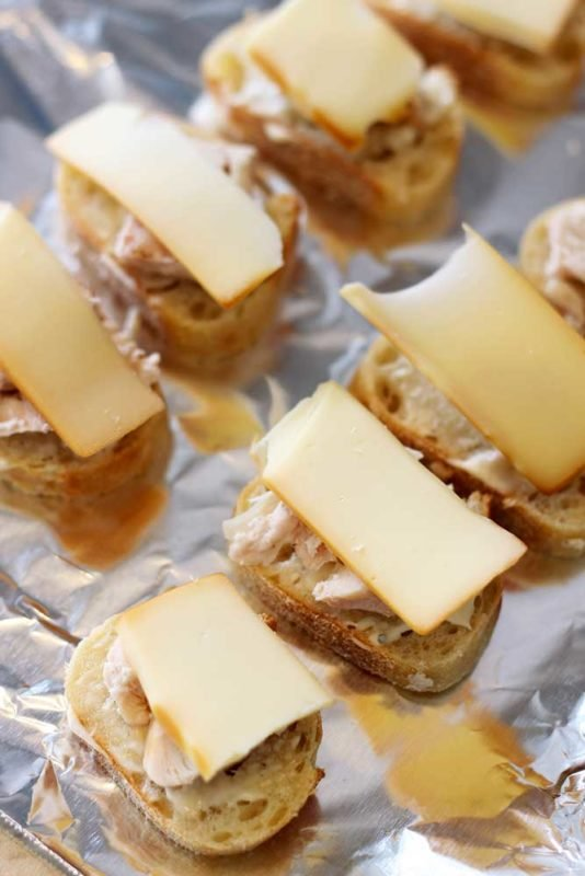 Garlic Mayo Chicken Baguettes sitting on an aluminum tray topped with Gruyère cheese.